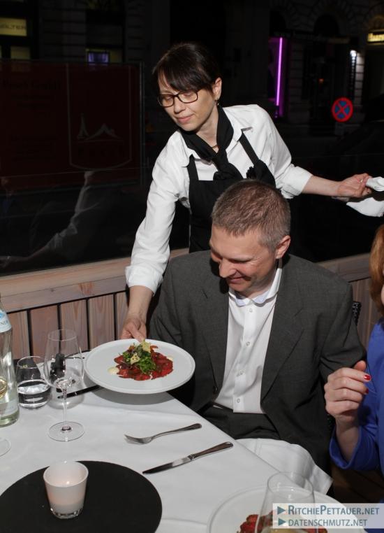 Service-Chefin Claudia serviert Manfred sein Carpaccio.